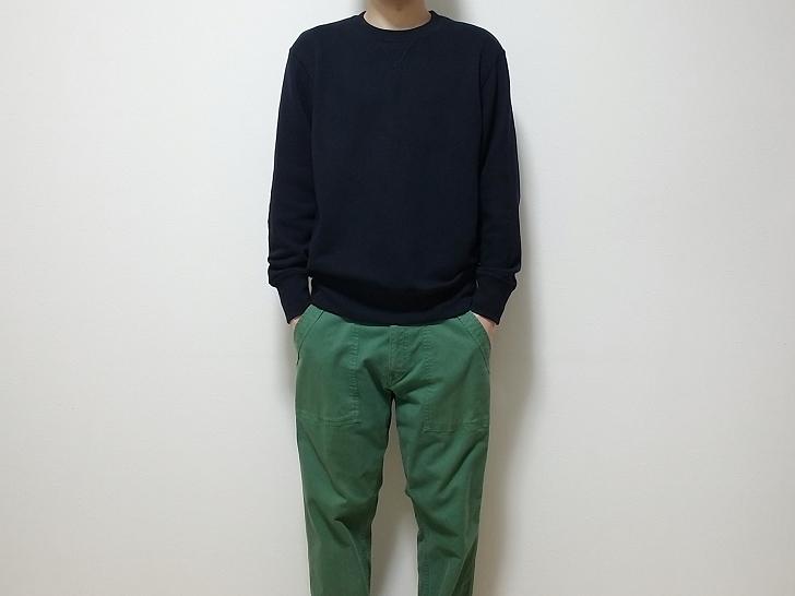 ネイビーのスウェットとグリーンのパンツを着た男性