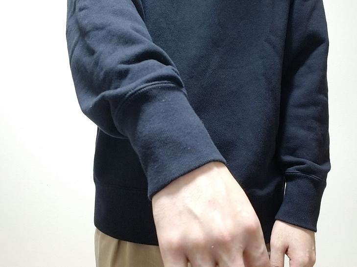 ユニクロのスウェットシャツを着た男性の手